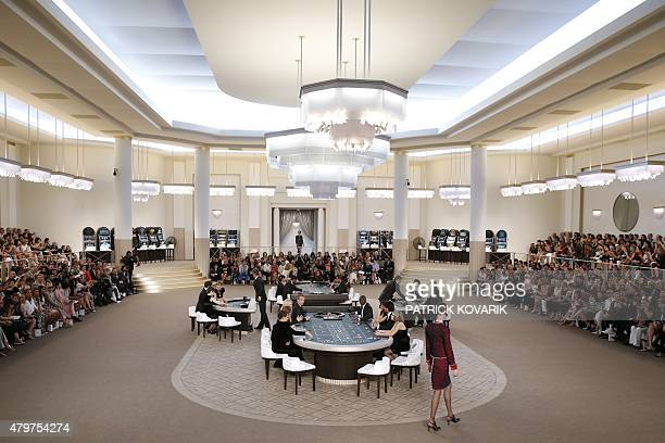 Models present creations for Chanel as guests sit around casino tables during the 20152016 fall/winter Haute Couture collection fashion show on July...