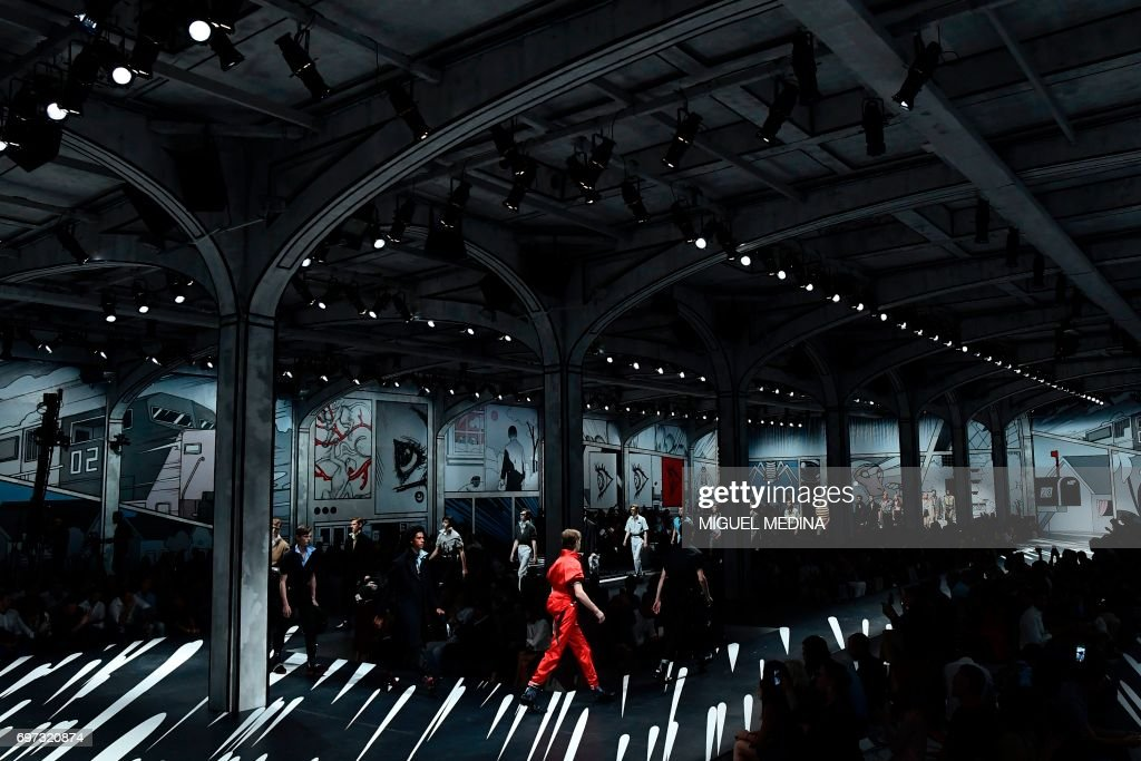 TOPSHOT - Models present creations for fashion house Prada during the Men's Spring/Summer 2018 fashion shows in Milan, on June 18, 2017. / AFP PHOTO / Miguel MEDINA