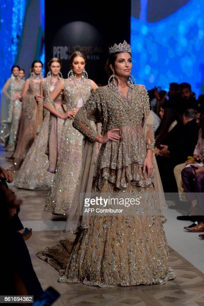 Models present creations of designer Ahmad Sultan during the second day of the Pakistan Fashion Design Council LOreal Paris Bridal Week in Lahore on...