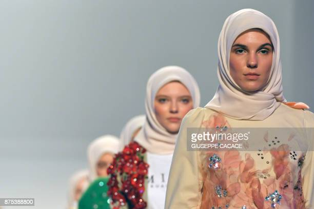 Models present on the catwalk a creation of Minaz during the Arab Fashion Week in the United Arab Emirate of Dubai on November 17 2017 / AFP PHOTO /...