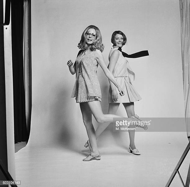 Models Sally Steward wearing a printed dacron and cotton playsuit with pleated culotte skirt with matching cover up by Carnegie and Suzy Kidd wearing...