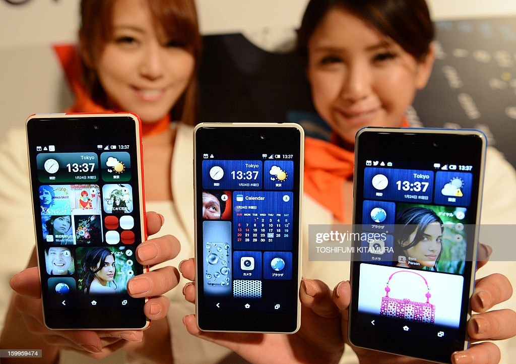 Models show off Japanese telecom operator KDDI's latest smartphones, the 'INFOBAR A02', during a press preview in Tokyo on January 24, 2013. Japan's mobile carrier KDDI will start selling the Naoto Fukasawa and Yugo Nakamura-designed stylish smartphone from mid-February. AFP PHOTO / TOSHIFUMI KITAMURA