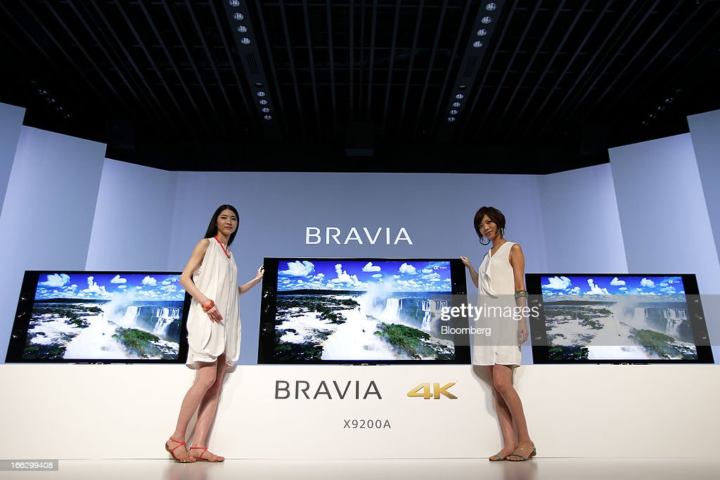 Models stand next to a display of Sony Corp. Bravia 4K liquid crystal display (LCD) televisions during at its launch in Tokyo, Japan, on Thursday, April 11, 2013. Sony is sticking with a goal of turning Japan's largest TV-manufacturing business profitable this fiscal year even as it continues losing global market share to Samsung Electronics Co. Photographer: Kiyoshi Ota/Bloomberg via Getty Images