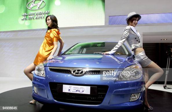 Models Stand Next To A New Hyundai Motor Co I30 At The
