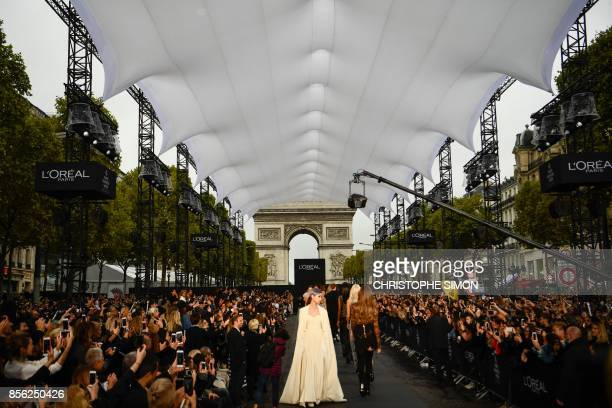 Models take part in the L'Oreal fashion show which theme is Paris on the sidelines of the Paris Fashion Week on October 1 on a catwalk set up on the...
