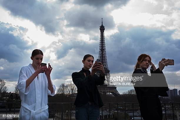 TOPSHOT Models take selfies backstage in front of the Eiffel Tower before the Ellery fashion show during the 20162017 fall/winter readytowear...