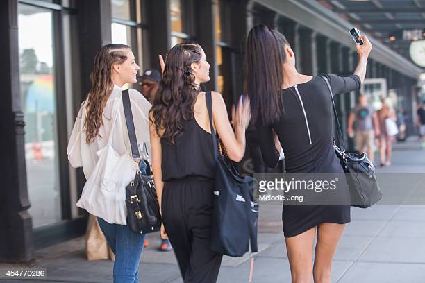 Models take selfies on Day 2 of New York Fashion Week Spring/Summer 2015 on September 5 2014 in New York City