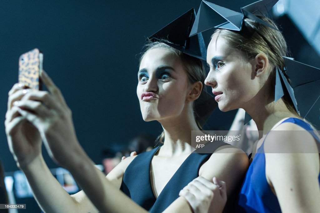 Models take their own snapshots backstage before presenting creations by Uma Raquel Davidowicz during the 2013 Summer collections of the Sao Paulo Fashion Week in Sao Paulo, Brazil, on March 22, 2013. AFP PHOTO / Yasuyoshi CHIBA