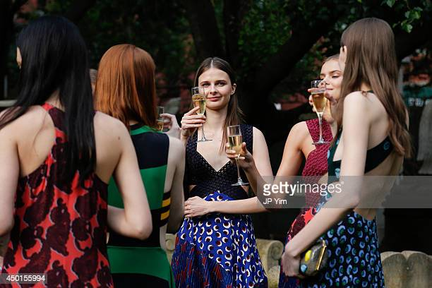 Models toast with champagne at the Stella McCartney Spring 2015 Presentation at Elizabeth Street Gardens on June 5 2014 in New York City