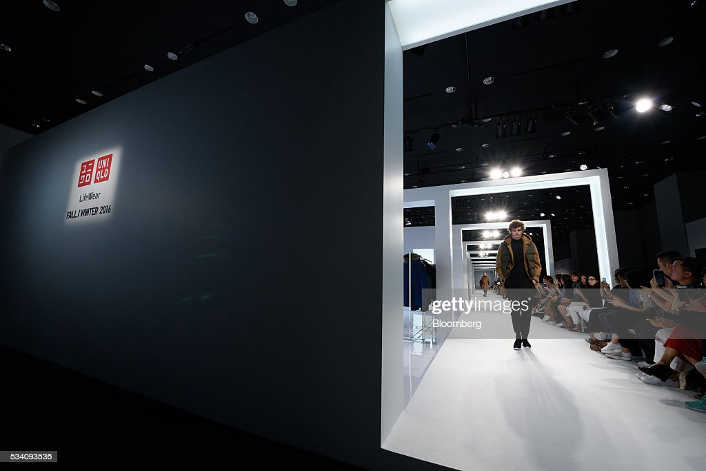 Models walk down the runway as attendees take photographs with their smartphones during a preview of Fast Retailing Co.'s Uniqlo 2016 Fall-Winter lineup in Tokyo, Japan, on Wednesday, May 25, 2016. Analysts and investors will be watching as Uniqlo unveils the new season's LifeWear line in Tokyo to see whether Chairman Tadashi Yanai will come through with his pledge to offer the 'lowest possible prices.' Photographer: Akio Kon/Bloomberg via Getty Images