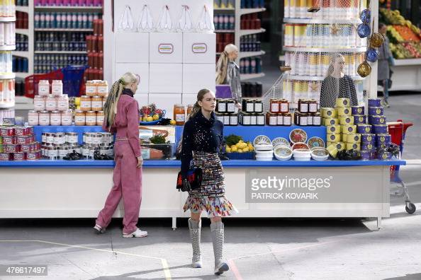 Models walk in a supermarket set up for the Chanel 2014/2015 Autumn/Winter readytowear collection fashion show on March 4 2014 at the Grand Palais in...