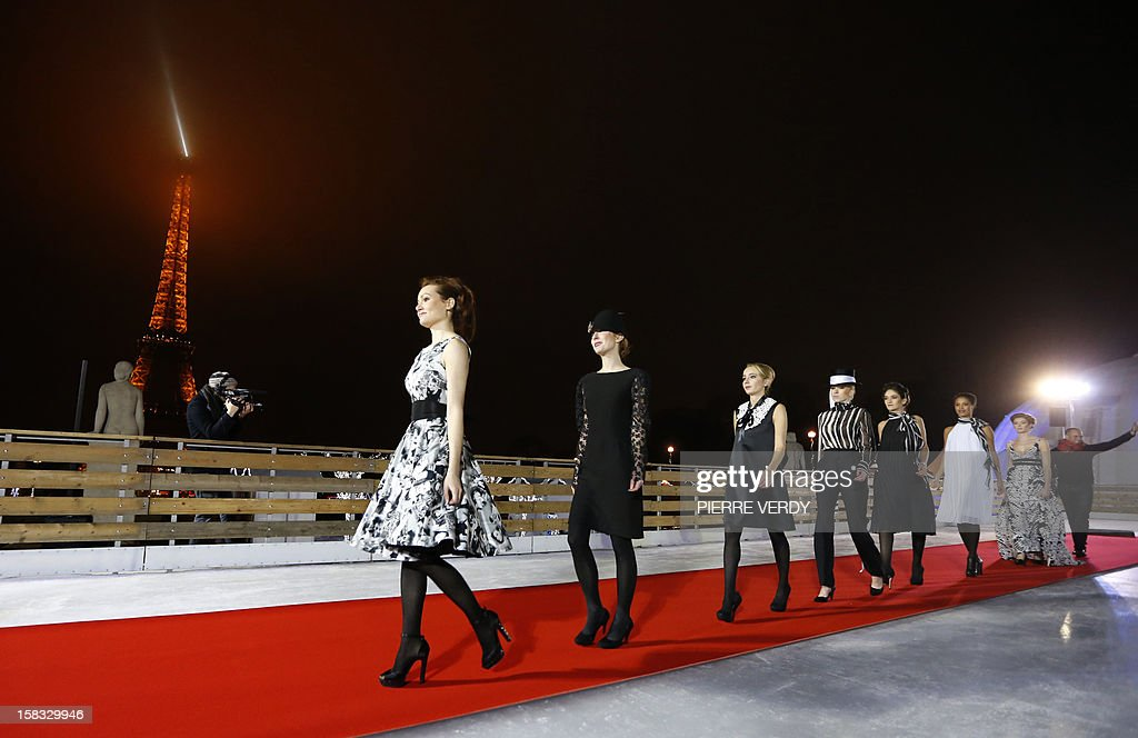 Models walk on a red carpet during the inauguration of the 'Christmas village', on December 13, 2012, in Paris, as part of the 'Trocadero On Ice' event. An ice-skating rink opened to public in front of the Eiffel tower, and will run until January 6, 2013. AFP PHOTO PIERRE VERDY