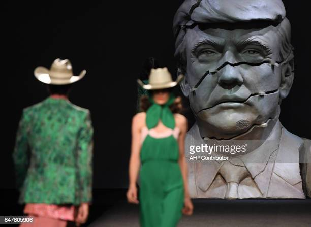 TOPSHOT Models walk on the catwalk with a cracked bust representing US president Donald Trump in the background during the presentation of Ana...