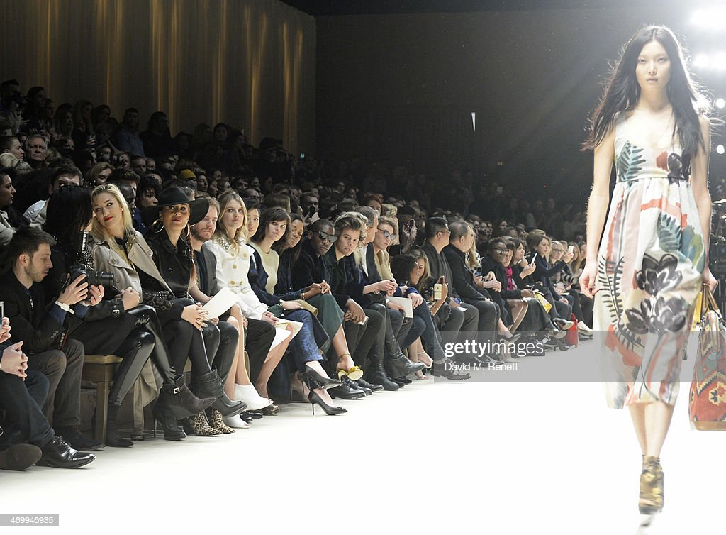 Models walk the runway as Donna Grantis, Hannah Welton, Ida Nielsen, Felicitas Rombold, Daniel Bruhl, Melanie Laurent, Guey Lun-Mei, Felicity Jones, Naomie Harris, Tinie Tempah, Harry Styles, Alison Mosshart, Mario Testino, Jamie Campbell Bower and Angelababy look on from the front row at Burberry Womenswear Autumn/Winter 2014 at Kensington Gardens on February 17, 2014 in London, England.