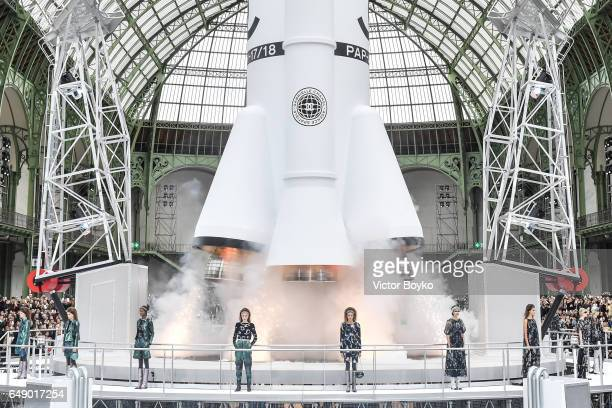 Models walk the runway designed as a space centre with a rocket taking off during the finale of the Chanel show as part of the Paris Fashion Week...