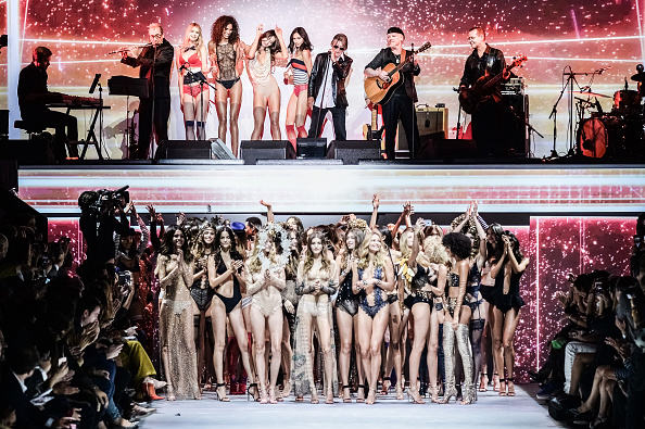 Models walk the runway while singer Jacques Dutronc performs on stage during the Etam show as part of the Paris Fashion Week Womenswear Spring/Summer...