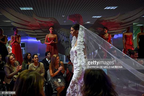 Models wear creations by designer Micaela Oliveira during a presentation by Portuguese football club Benfica of 24 wedding dresses 12 evening dresses...