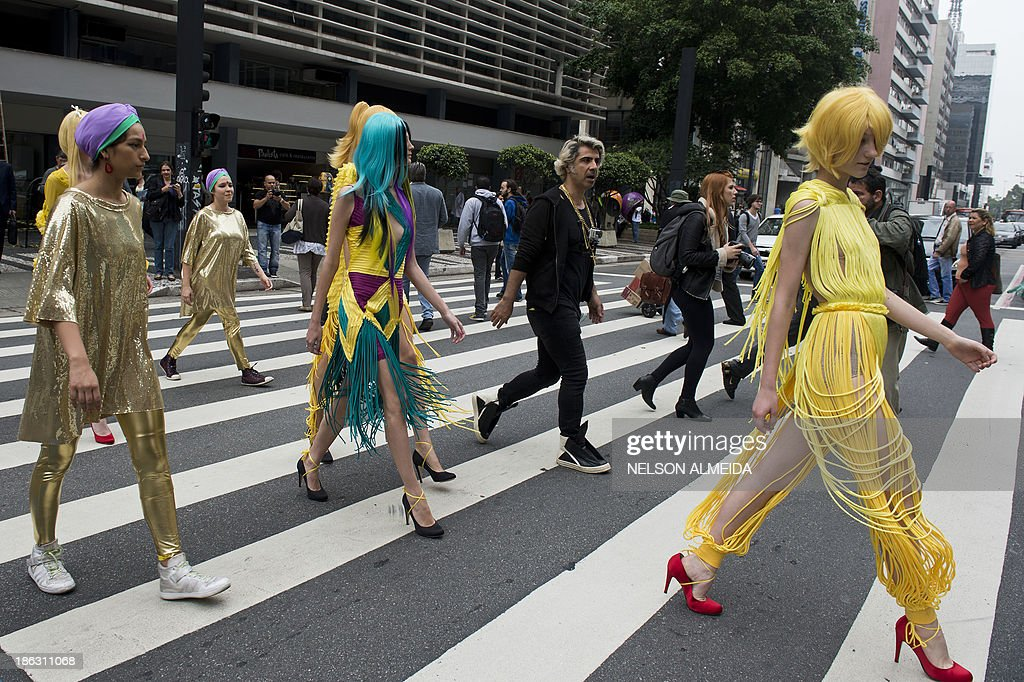 Models wear creations by FH for Fause Haten along Paulista Avenue during the presentation of the 2014 Winter collections of the Sao Paulo Fashion Week in Sao Paulo, Brazil, on October 30, 2013. AFP PHOTO / Nelson ALMEIDA