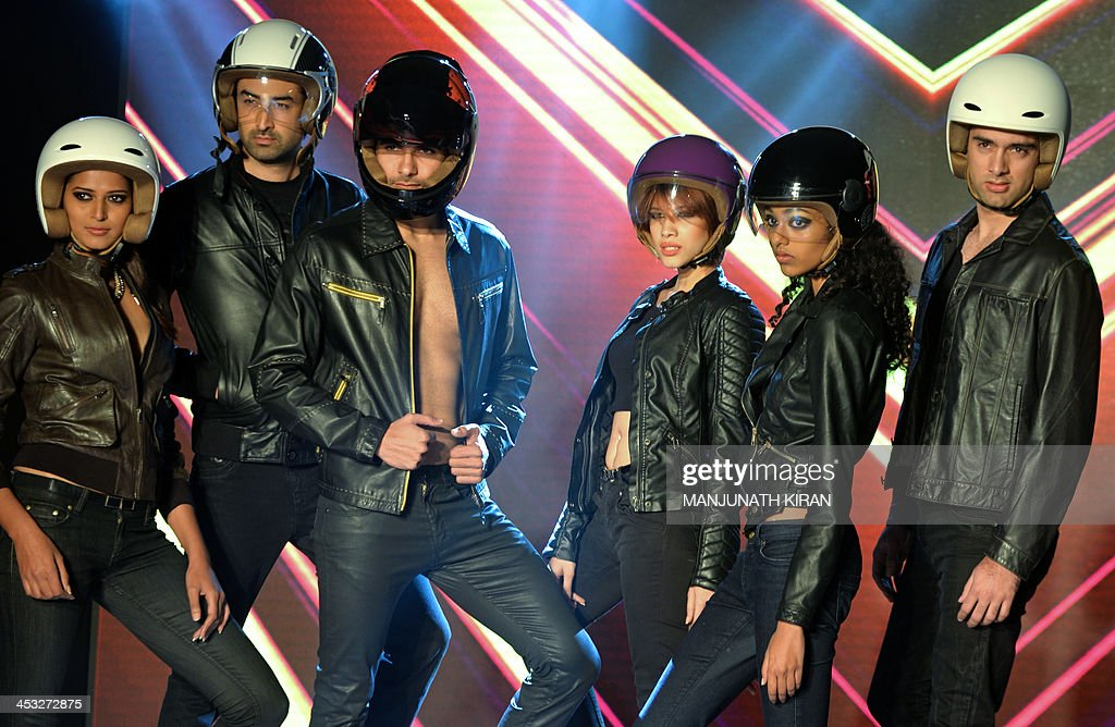 Models wearing Fastrack motorcycle helmets pose during the launch in Bangalore on December 3, 2013. Fastrack, a youth accessories brand of Titan Industries Limited, launched helmets manufactured in India in technical collaboration with Italy's AGV brand helmets. AFP PHOTO/Manjunath KIRAN
