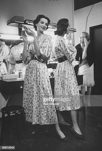 Models wearing identical Claire McCardell floral print dresses w new longer length skirt inspired by designer Christian Dior and w shorter skirt at...
