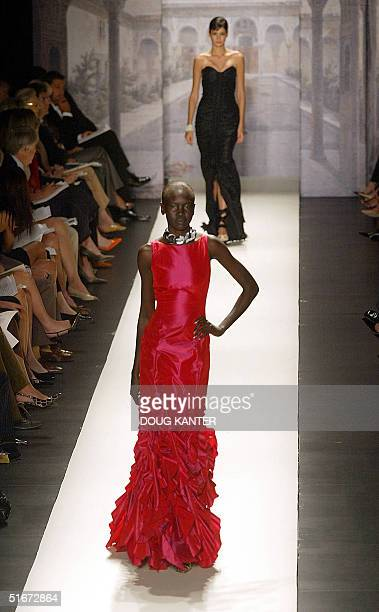 Models wears a silk taffeta gown with ruffled hem and black silk taffeta embroidered gown at the Oscar de la Renta Spring 2003 fashion show in New...