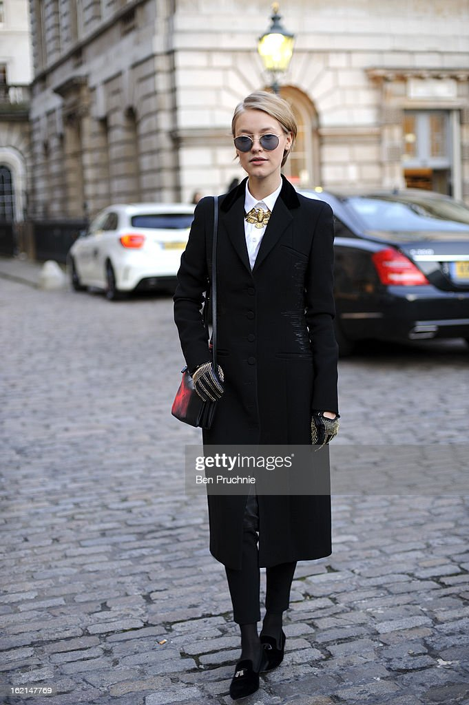 Model/Stylist/Photographer Onatia Romano poses wearing a Botega Venetta coat, Guisepe Zanoti shoes with a Vintage necklace, Celine Shirt, Ralph Lauren glasses and a Celine Bag with Burberry Gloves at Somerset House during London Fashion Week on February 19, 2013 in London, England.