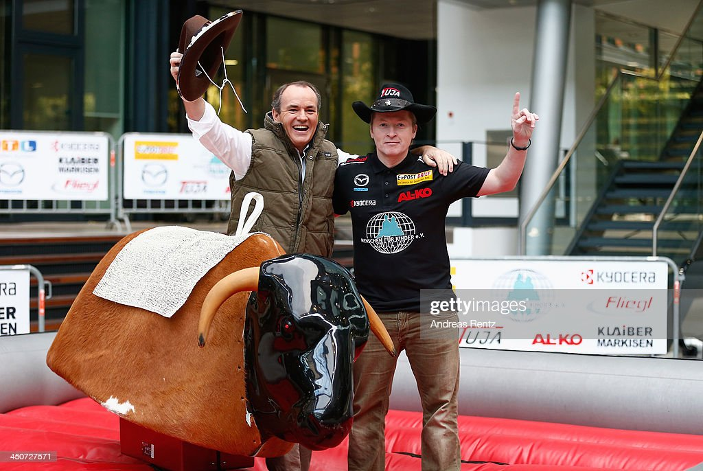 Moderator Wolfram Kons (L) and Joey Kelly (R) pose on a bull riding machine during a photocall on November 20, 2013 in Cologne, Germany. Joey Kelly will go riding 24 hours non stop during the RTL Spenden Marathon on November 22.