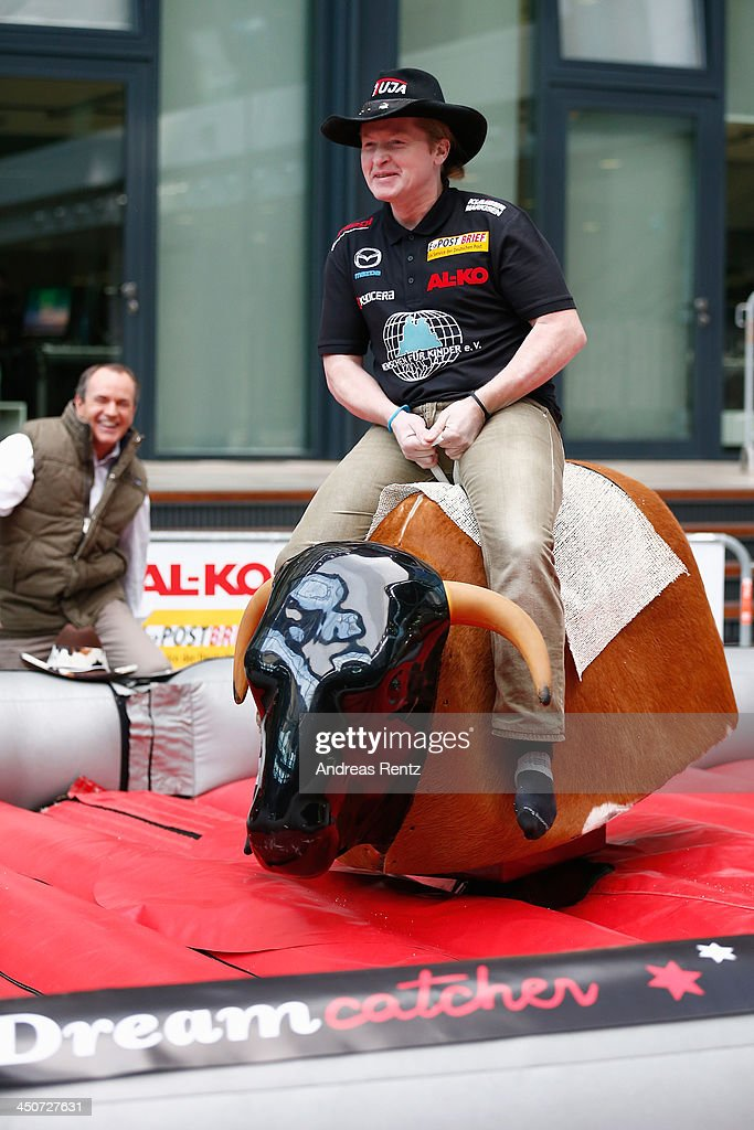 Moderator Wolfram Kons (L) smiles as Joey Kelly (R) rides on a bull riding machine during a photocall on November 20, 2013 in Cologne, Germany. Joey Kelly will go riding 24 hours non stop during the RTL Spenden Marathon on November 22.