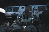 Modern aircraft flight instruments and levers in cockpit.