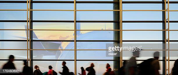Modern airport terminal, travellers in silhouette