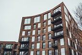 Low Angle Architectural Exterior View of Modern Low Rise Residential Apartment Building with Small Balconies and Curved Facade on Gloomy Overcast Gray Day