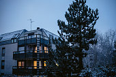 Modern apartment with one light turned on the second and third window floors and beautiful pine tree - snow falling in December