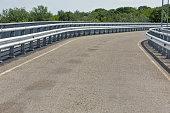 Modern asphalt road with metal guard rails and walkway for pedestrians, closeup