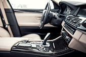 Modern beige and black interior of modern car, close-up details of automatic transmission and gear stick against steering wheel background and dashboard