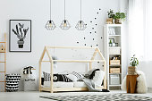 Modern baby bedroom in white with bed, bookcase, and carpet