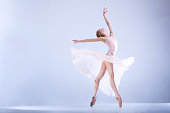 Young ballerina in a light dress is dancing in a white studio full of light