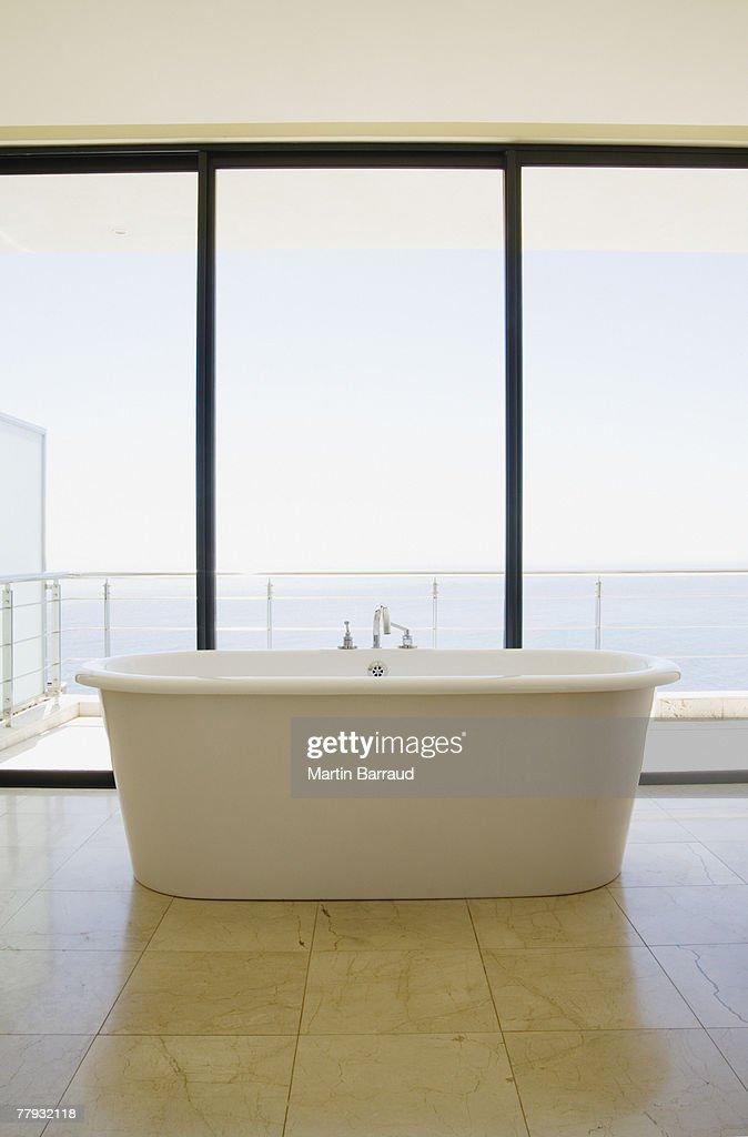Modern bathroom with bathtub and large windows : Stock Photo