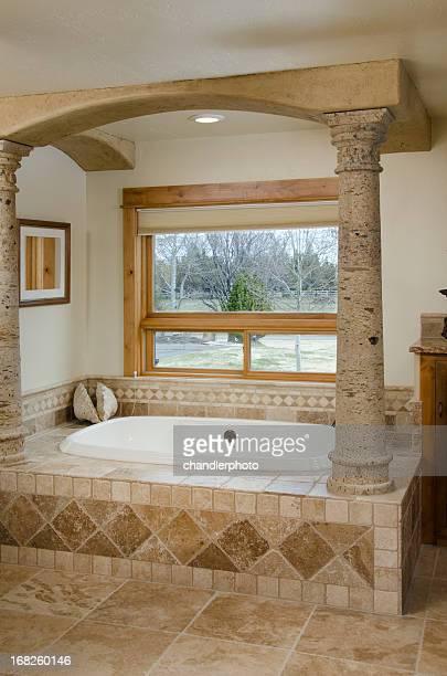 Modern bathroom with pillars and sunken bathtub