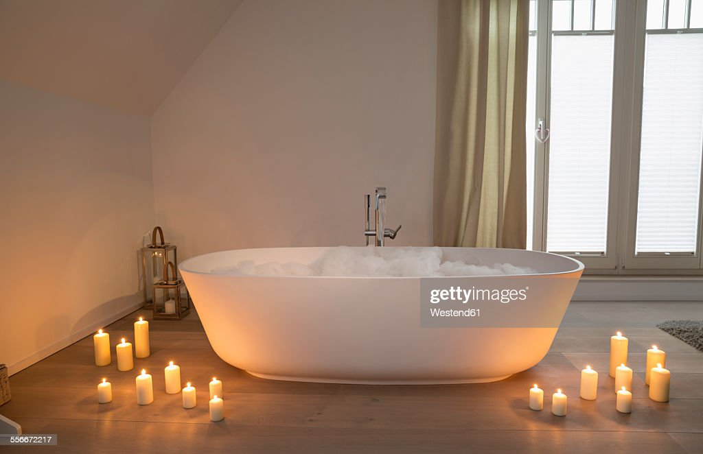 Modern bathtub with lighted candles arround : Stock Photo