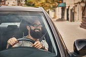 A Young attractive man driving a vehicle, looking at scenery, seen through the windshield glass. Happy driver, holding hands on the steering wheel with a wide beautiful smile.
