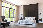 Modern bedroom decorate with  brown leather furniture and black wood 3d rendering image.There are large window overlooking to nature and forest