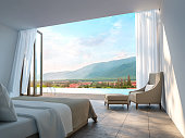 Modern Bedroom with mountain view 3d rendering Image. There are borderless swimming pool There are large open door overlooking the surrounding nature and mountains
