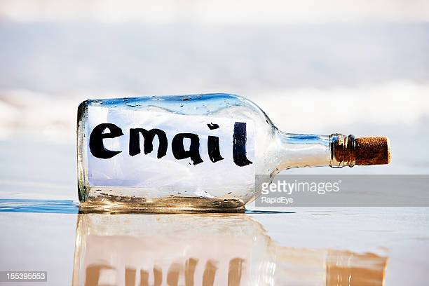 Modern bottle on beach in close up holds email message