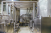 Modern brewery interior. Filtration vats, pipeline, valves and other equipment of beer production line.