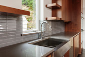 Modern sleek bright kitchen with an undermounted farmhouse type sink with a view, subway tile backsplash, brown cabinets and water faucet