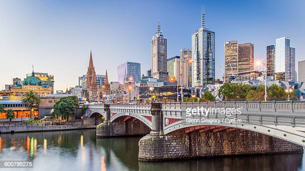 Modern Buildings In Front Of Yarra River Against Clear Sky At Dusk