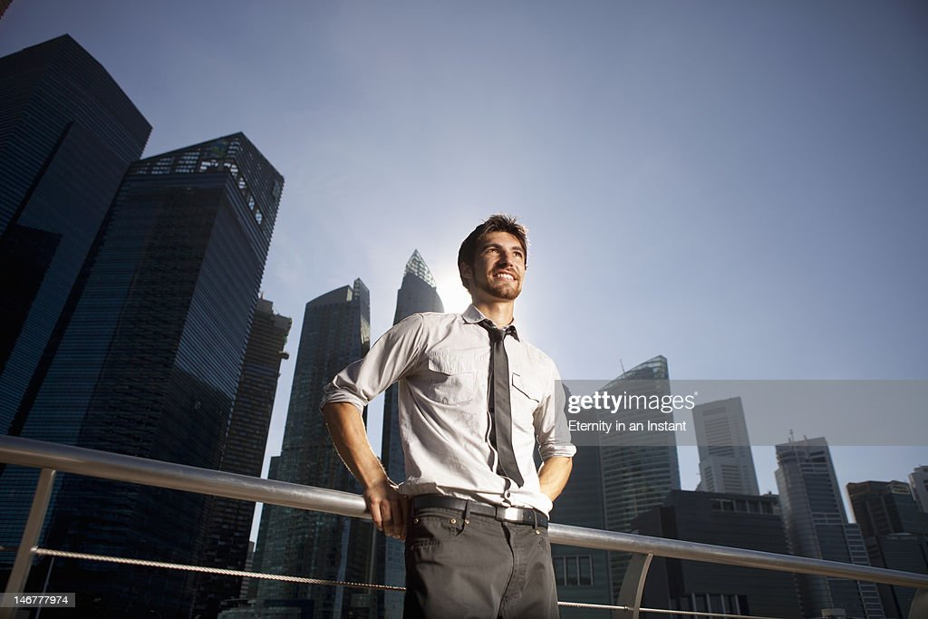 Modern businessman in city, smiling : Stock Photo