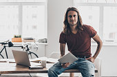 Handsome young man with long hair holding digital tablet and looking at camera with smile while leaning at the desk in creative office