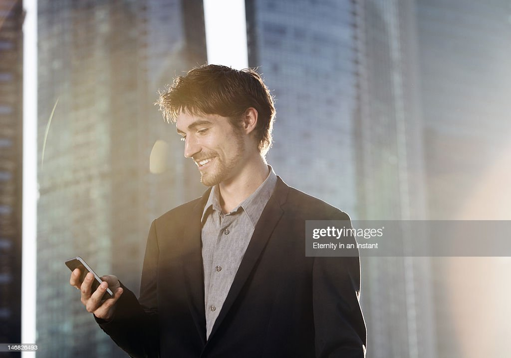 Modern businessman using smartphone in city : Stock Photo