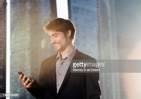 Modern businessman using smartphone in city : Stock Photo